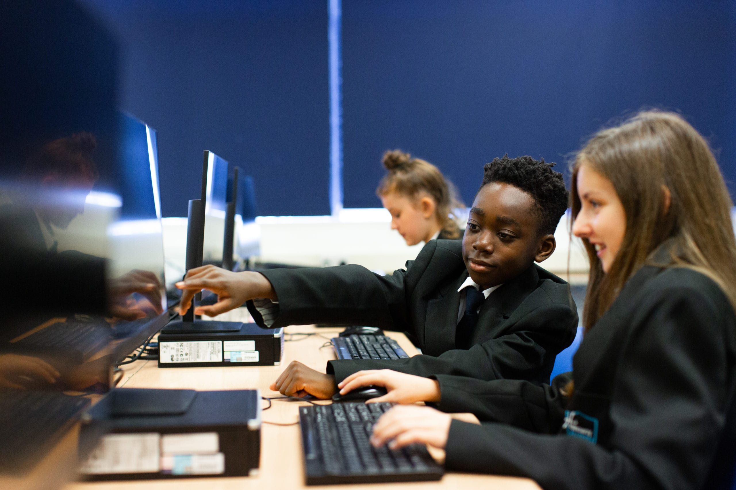Pupils using a computer supporting each other